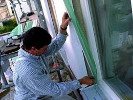 Handwerker beim Anschluss neuer Fenster an die Fassadendämmung